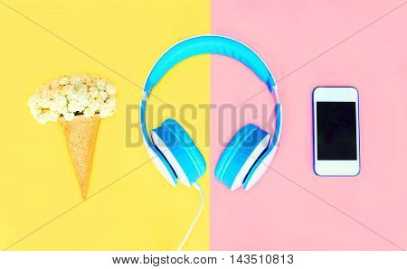 Headphones With Ice Cream Cone Flowers White Smartphone Over Colorful Yellow Pink Background