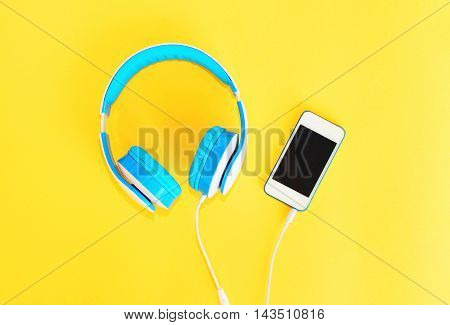 Headphones Connected To White Smartphone Over Yellow Background