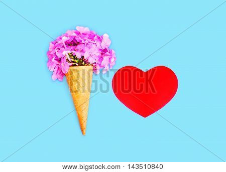 Ice Cream Cone With Flowers And Red Heart Shape Over Blue Colorful Background Top View
