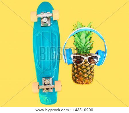 Pineapple With Headphones Sunglasses And Skateboard Over Colorful Yellow Background