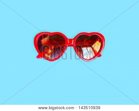 Red Sunglasses With Heart Shape Over Colorful Blue Background