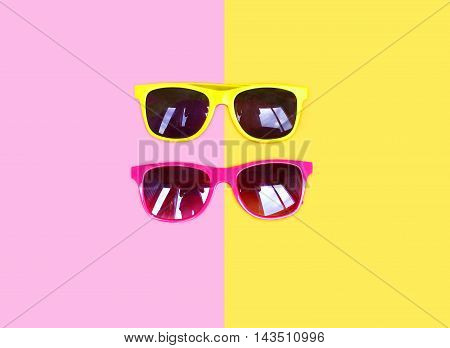 Two Sunglasses Yellow Pink Over A Colorful Background