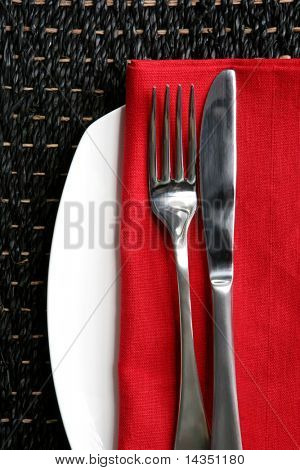 Place setting ~ knife and fork on red napkin and white plate, against bamboo placemat.