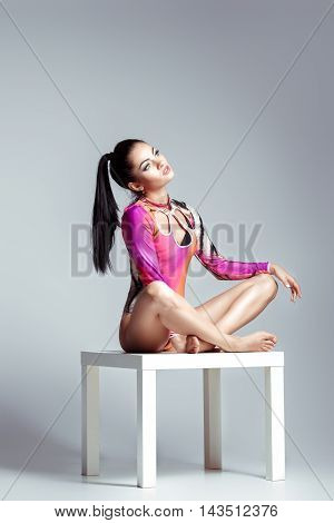 sexy woman in bodysuit with perfect sporty body posing at Studio