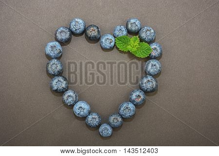 On a dark background  blueberries ligned up in the shape of a heart and decorated with mint leaf.