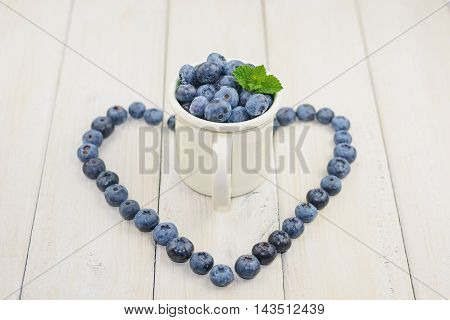 Blueberries are laid out on the table in the form of heart around a cup full of berries.