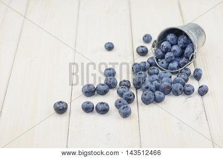Reversed aluminum bucket with crumbled blueberries on white wooden background.