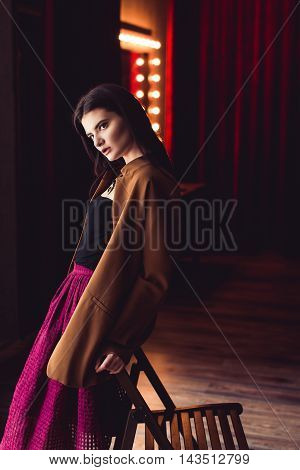 portrait of young brunette model woman posing in fashionable clothes in burlesque fitting room