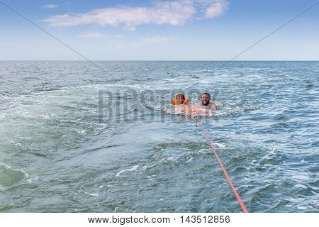 Man with a child girl swimming on lap attached to the ship