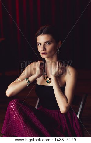 indoor shot of young brunette model posing in fashionable clothes in burlesque fitting room