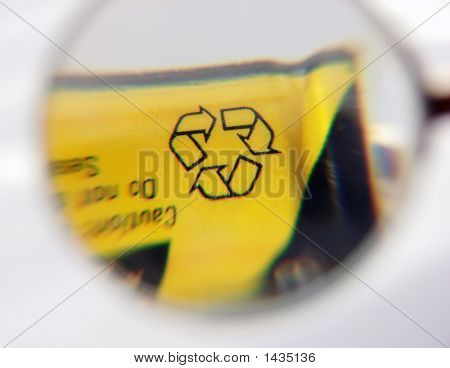 Recycle Symbol On A Battery Close Up With A Magnifier.
