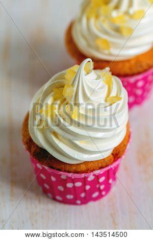 Fresh lemon cupcakes with Swiss meringue closeup.