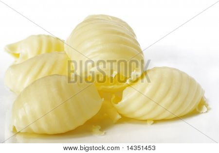 Butter curls, on a reflective white surface.