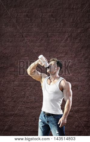 young man with strong muscles water drink after training -- toned and stylized photo