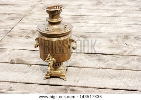 brass old samovar on a wooden table closeup