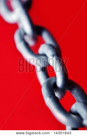Abstract of galvanized chain links, with vibrant red background.  Shallow DOF.