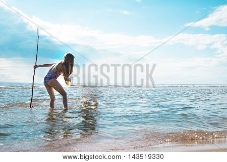 girl with a trident in his hand standing in the sea