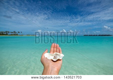 Open shell with a pearl on tropical beach in the woman's hand