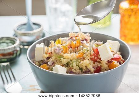 Pouring vegetable oil into the plate with colorful quinoa salad with goat cheese on blue vintage wooden table