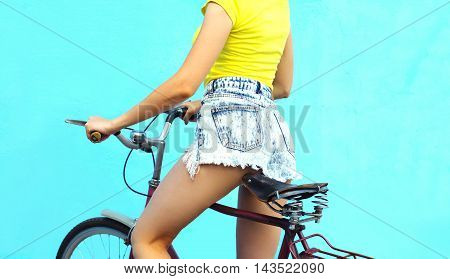 Fashion Pretty Woman In Jeans Shorts On Bicycle Over Colorful Blue Background Closeup