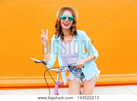Fashion Pretty Woman With Bicycle Over Colorful Orange Background