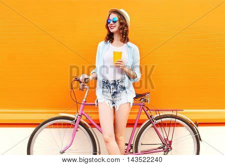 Fashion Pretty Woman With Coffee Or Juice Cup And Retro Vintage Bicycle Over Colorful Orange Backgro