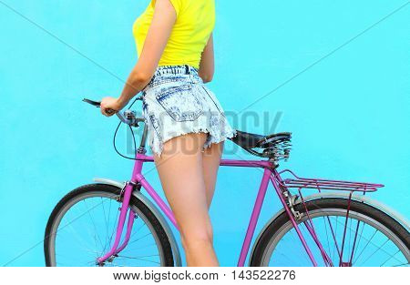 Fashion Pretty Young Woman In Jeans Shorts On Bicycle Over Colorful Blue Background Closeup