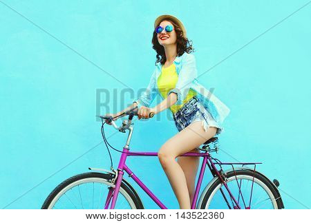 Happy Pretty Smiling Woman Rides A Bicycle Over Colorful Blue Background In Profile