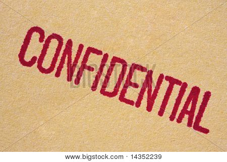 """Confidential"" stamp on manila paper.  Macro view, with red ink bleeding into paper."