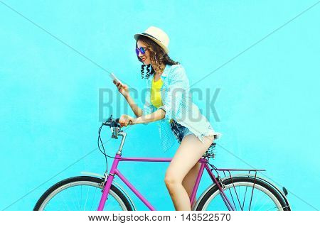 Pretty Cool Smiling Woman Using Smartphone On Retro Bicycle Over Colorful Blue Background In Profile