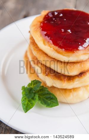 Stack Of Cheesecakes With Jam On A White Plate On A Dark Wooden Background