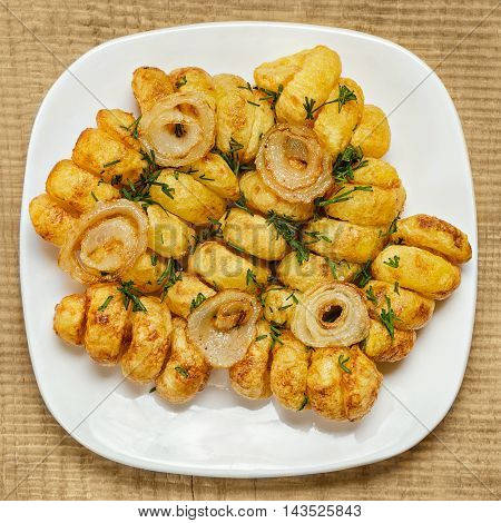 Fried potatoes cut in a spiral, on a white plate and wooden background