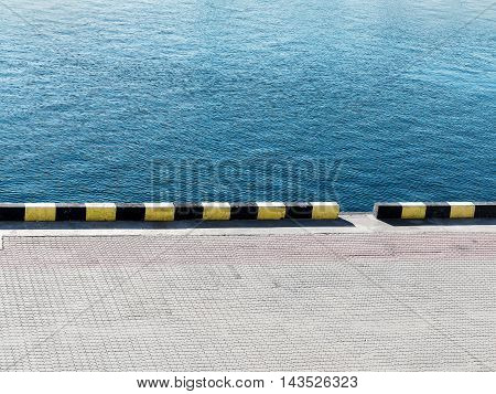 Textured Background Of Sea Water And A Pier In The City Seaport