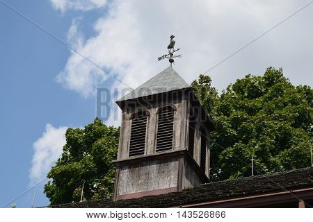 a wooden cupola with weather vane against a cloudy blue sky.