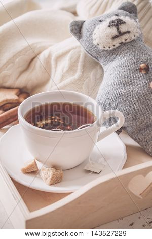 Tea tray and sweater, white wood background, toned