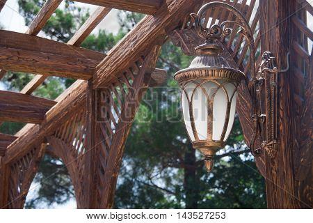 Vintage street light on wooden beams in the metal frame.