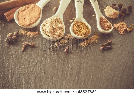 Selection of spices for christmas and thanksgiving, white wood background, copy space, toned
