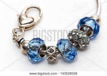 A metal bracelet with three blue stones