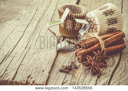 Selection of christmas spices on rustic wood background, top view, toned