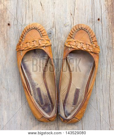 a pair of old worn orange female shoes made of genuine leather on old gray wooden board with cracks