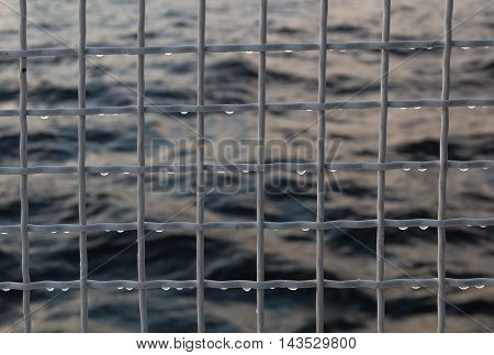 Metallic net with drops against sea background