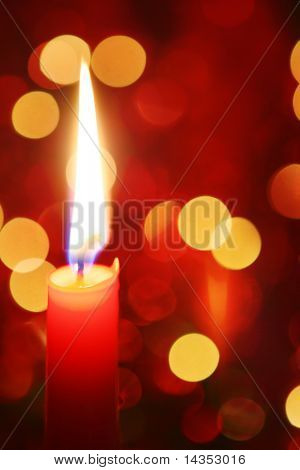 Red candle burning, with defocussed fairy lights behind.  Festive Christmas background.