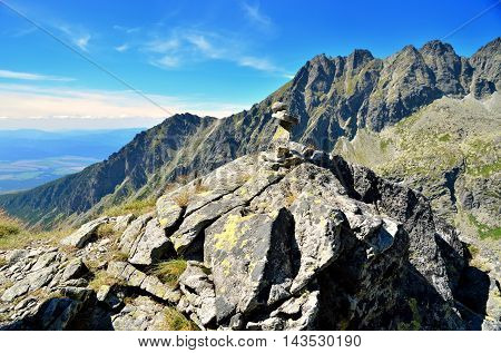 Summer mountain landscape. Mound of stones with mountains peaks in the background. Shallow depth of field.