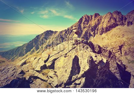 Summer mountain landscape in vintage style. Mound of stones with mountains peaks in the background. Shallow depth of field.