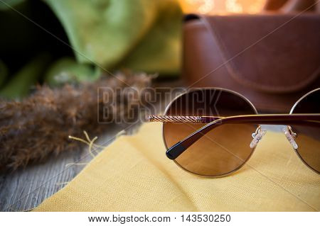 sunglasses lying on the wooden desk with leather box , style isolated subject photo,