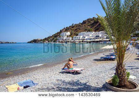 LOUTRO, CRETE, GREECE - JULY 2016: Woman in bikini is sitting at stone beach of loutro town on Crete island, Greece