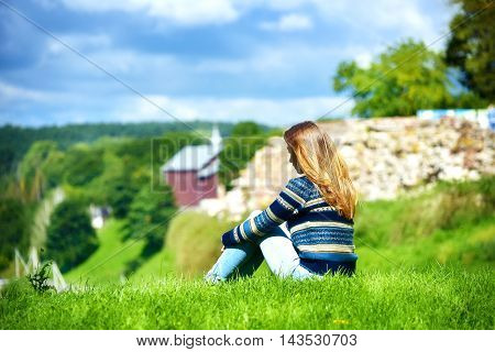 Pensive young girl on a green hilltop.