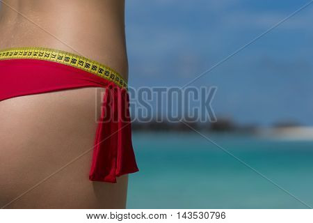 Sexy Female Buttocks With A Tape Measure On The Beach. The Concept Of Diet And Healthy Lifestyle.