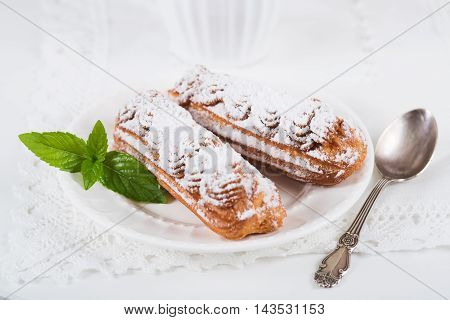 Eclairs on plate on a table on light background