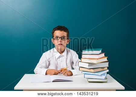 Cute little boy with books on the table blue background